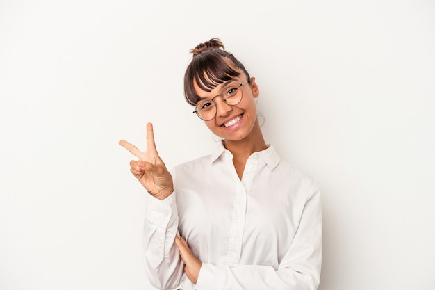 Young mixed race business woman isolated on white background  joyful and carefree showing a peace symbol with fingers.
