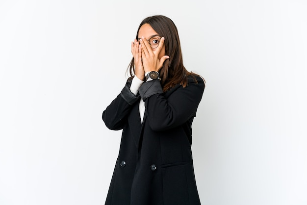 Young mixed race business woman isolated on white blink through fingers frightened and nervous.
