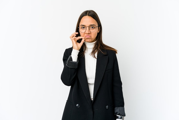 Young mixed race business woman isolated on white space with fingers on lips keeping a secret.