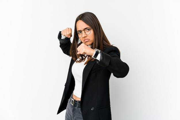 Young mixed race business woman isolated on white wall throwing a punch, anger, fighting due to an argument, boxing.