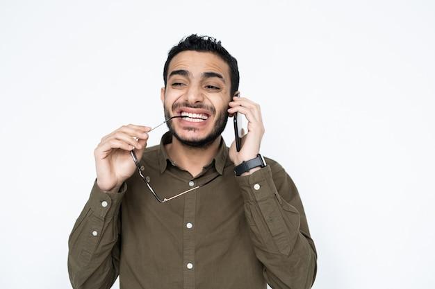 クライアントや同僚と孤立して話している耳と眼鏡でスマートフォンを持つ若い混血のビジネスマン