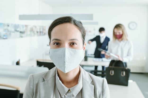 仕事に行く彼らの机のそばで彼女の同僚と保護マスクで若い混血の実業家