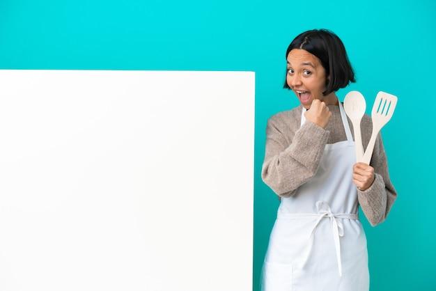 勝利を祝う青い背景に分離された大きなプラカードを持つ若い混血料理人の女性