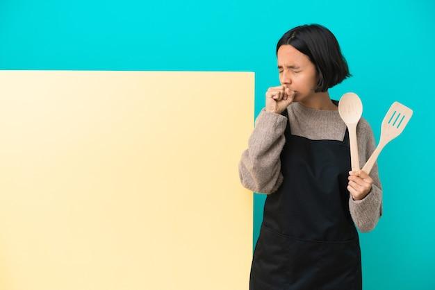 기침을 많이 하는 파란색 배경에 격리된 큰 플래카드를 가진 젊은 혼혈 요리사 여성