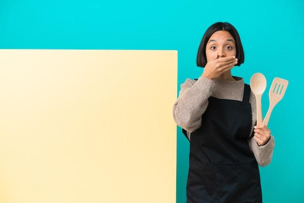 手で口を覆っている青い背景に分離された大きなプラカードを持つ若い混血料理人女性