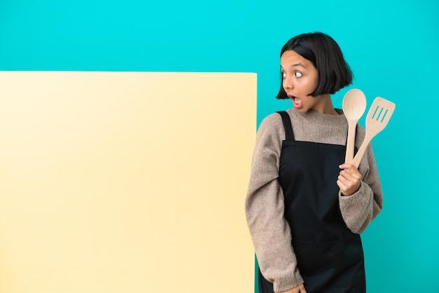 Молодая женщина-повар смешанной расы с большим плакатом, изолированным на синем фоне, делает неожиданный жест, глядя в сторону