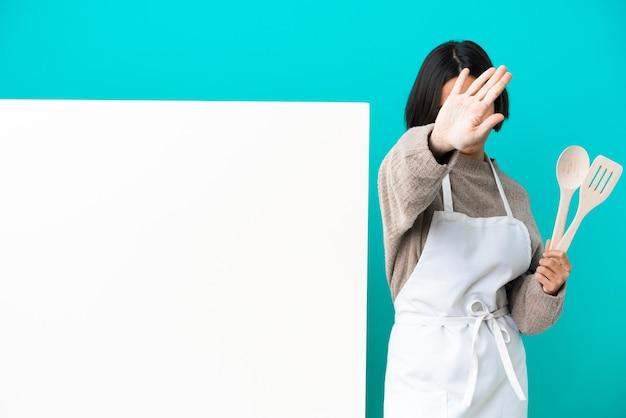 顔に焦点を当てて青い背景に分離された大きなプラカードを持つ若い混血料理人の女性。フレーミングシンボル
