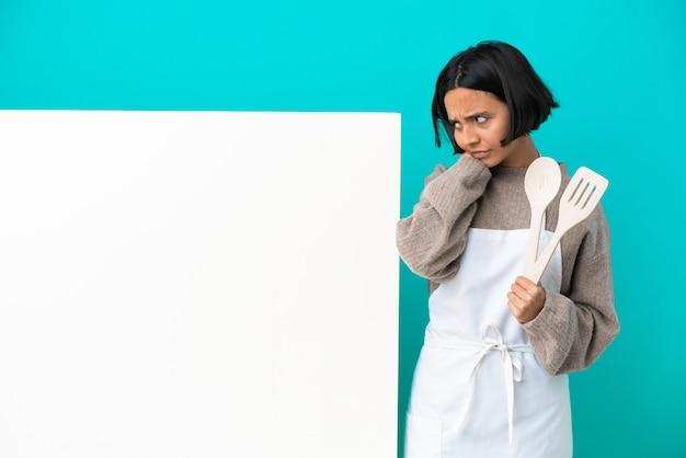 欲求不満と耳を覆う青い背景に分離された大きなプラカードを持つ若い混血料理人の女性