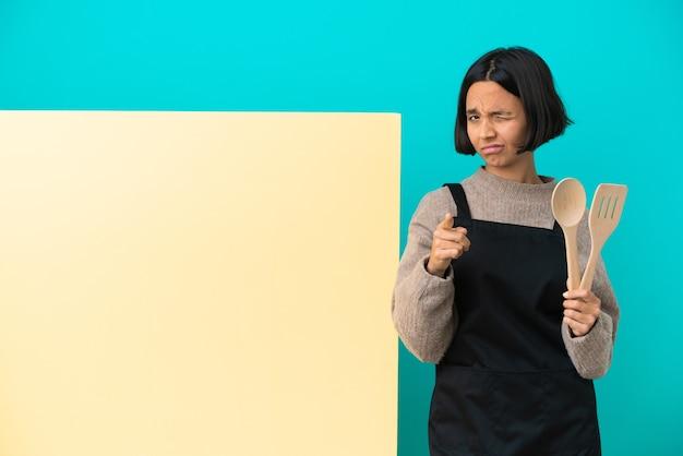 欲求不満と正面を指している青い背景に分離された大きなプラカードを持つ若い混血料理人の女性