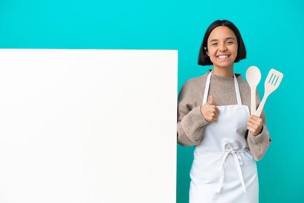 親指を立てるジェスチャーを与える青い背景に分離された大きなプラカードを持つ若い混血料理人の女性