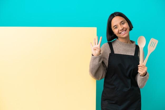 幸せで、指で4を数える青い背景で隔離の大きなプラカードを持つ若い混血料理人の女性