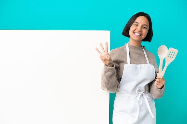 파란색 배경에 행복하고 손가락으로 세 세에 고립 된 큰 현수막을 가진 젊은 혼합 된 경주 요리사 여자
