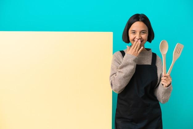 青い背景に分離された大きなプラカードを持つ若い混血料理人女性幸せと笑顔の手で口を覆う