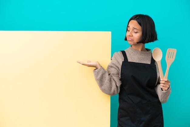 広告を挿入するために手のひらに架空のコピースペースを保持している青い背景に分離された大きなプラカードを持つ若い混血料理人の女性