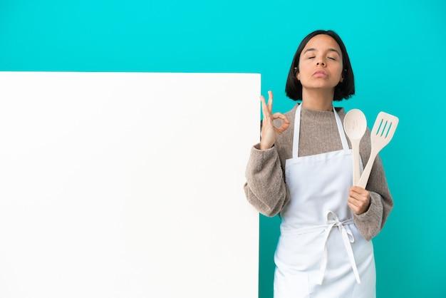 禅のポーズで青い背景に分離された大きなプラカードを持つ若い混血料理人の女性