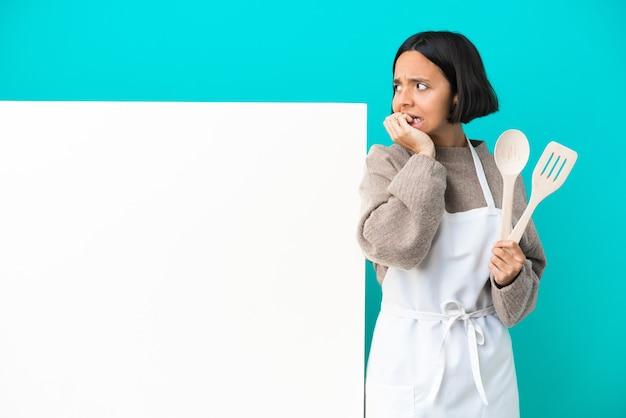 青い背景に分離された大きなプラカードを持つ若い混血料理人の女性は少し緊張しています