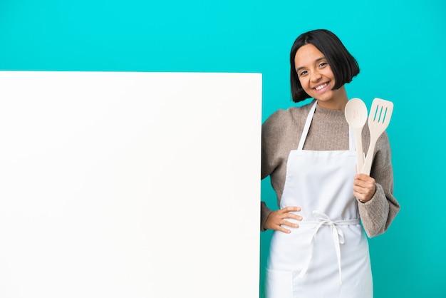腕を正面の位置で交差させたまま青い背景に分離された大きなプラカードを持つ若い混血料理人の女性