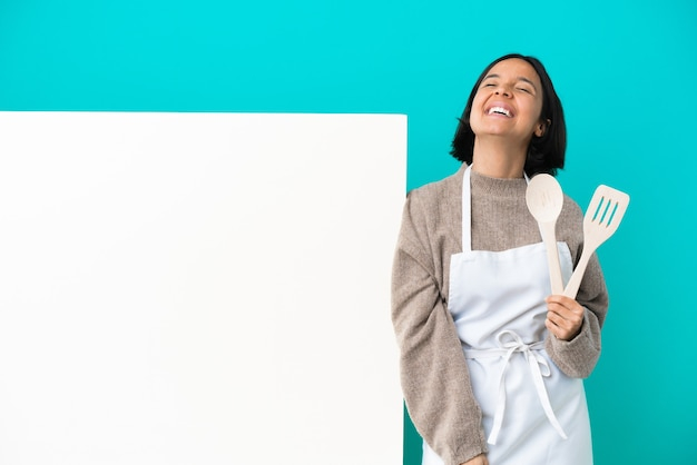 笑って青い背景に分離された大きなプラカードを持つ若い混血料理人の女性