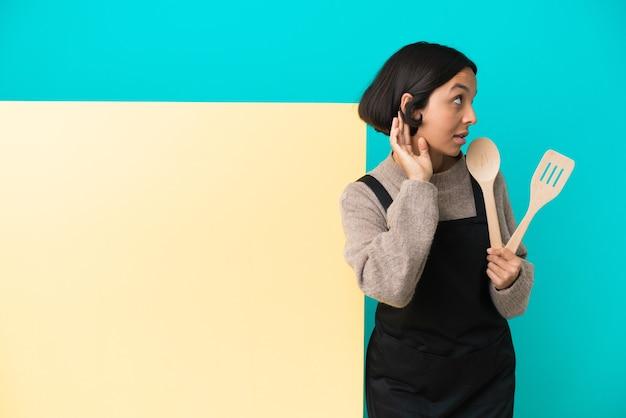 귀에 손을 넣어 뭔가를 듣고 파란색 배경에 고립 된 큰 현수막을 가진 젊은 혼합 된 경주 요리사 여자