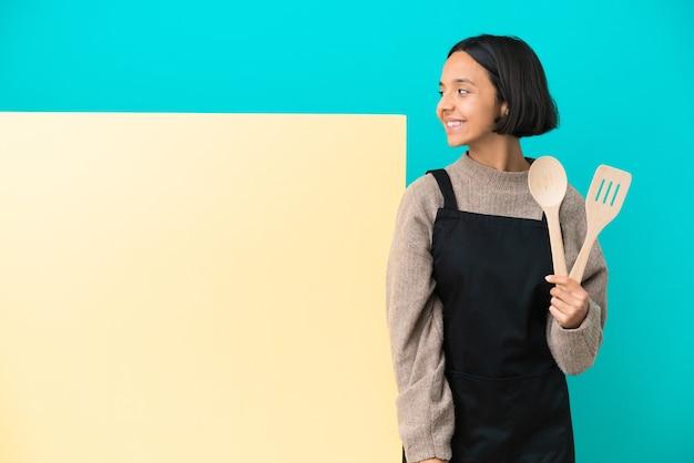 Молодая женщина-повар смешанной расы с большим плакатом на синем фоне смотрит в сторону и улыбается