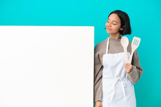 Молодая женщина-повар смешанной расы с большим плакатом, изолированным на синем фоне, глядя в сторону