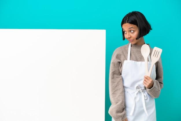 青い背景に分離された大きなプラカードを持つ若い混血料理人の女性