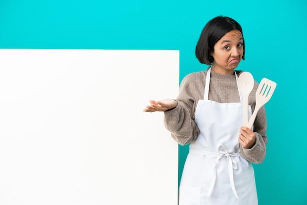青い背景に分離された大きなプラカードを持つ若い混血料理人の女性は、肩を持ち上げながらジェスチャーを疑う