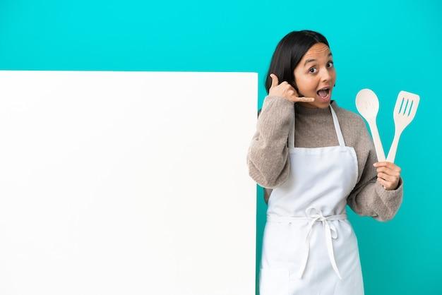 Молодая женщина-повар смешанной расы с большим плакатом, изолированным на синем фоне, делая жест по телефону и сомневаясь