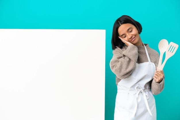 愛らしい表情で睡眠ジェスチャーを作る青い背景に分離された大きなプラカードを持つ若い混血料理人の女性