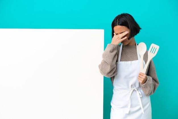 停止ジェスチャーを作成し、顔を覆う青い背景に分離された大きなプラカードを持つ若い混血料理人の女性
