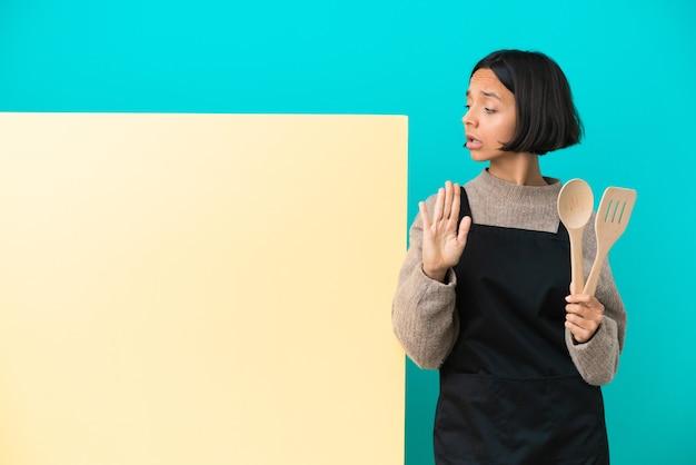 青い背景に分離された大きなプラカードを持つ若い混血料理人の女性が停止ジェスチャーを作成し、失望した