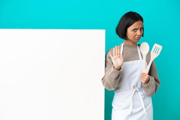 停止ジェスチャーを作る青い背景で隔離の大きなプラカードを持つ若い混血料理人の女性
