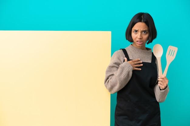 自分を指している青い背景に分離された大きなプラカードを持つ若い混血料理人の女性