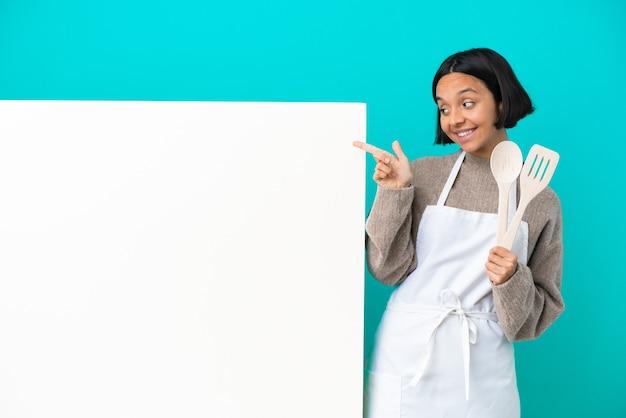 검지 손가락으로 좋은 생각을 가리키는 파란색 배경에 고립 된 큰 현수막을 가진 젊은 혼합 된 경주 요리사 여자