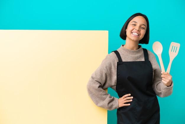 腰に腕と笑顔でポーズをとって青い背景に分離された大きなプラカードを持つ若い混血料理人の女性