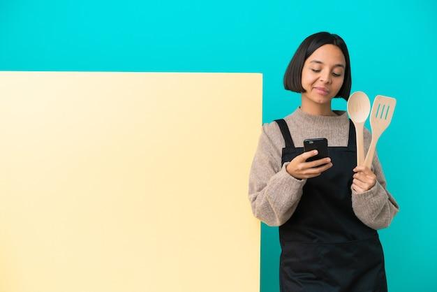 모바일로 메시지를 보내는 파란색 배경에 고립 된 큰 현수막을 가진 젊은 혼합 된 경주 요리사 여자