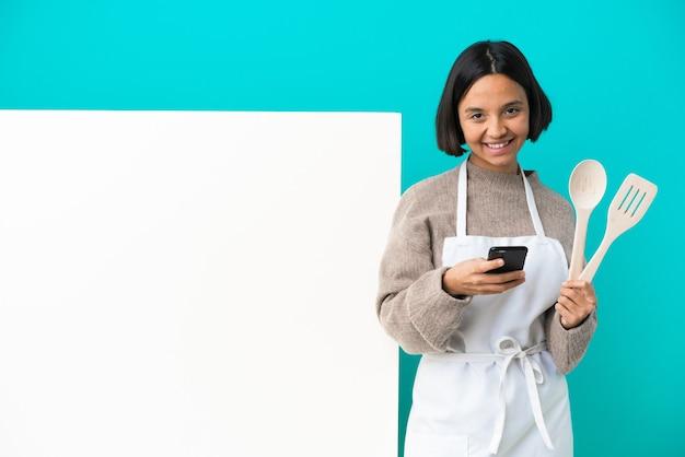 Молодая женщина-повар смешанной расы с большим плакатом, изолированным на синем фоне, отправляет сообщение с мобильного телефона