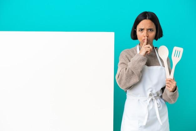 침묵 제스처의 기호를 보여주는 파란색 배경에 고립 된 큰 현수막을 가진 젊은 혼합 된 경주 요리사 여자