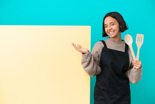 たくさん笑って青い背景に分離された大きなプラカードを持つ若い混血料理人の女性
