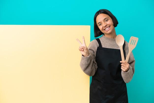 笑顔と勝利のサインを示す青い背景に分離された大きなプラカードを持つ若い混血料理人の女性