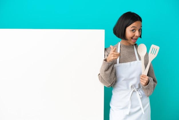 青い背景に分離された大きなプラカードを持つ若い混血料理人の女性は驚いて正面を指しています