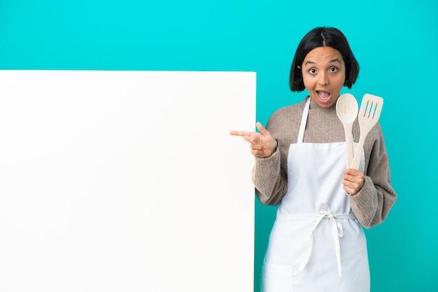 青い背景に分離された大きなプラカードを持つ若い混血料理人の女性は驚いて、側を指しています
