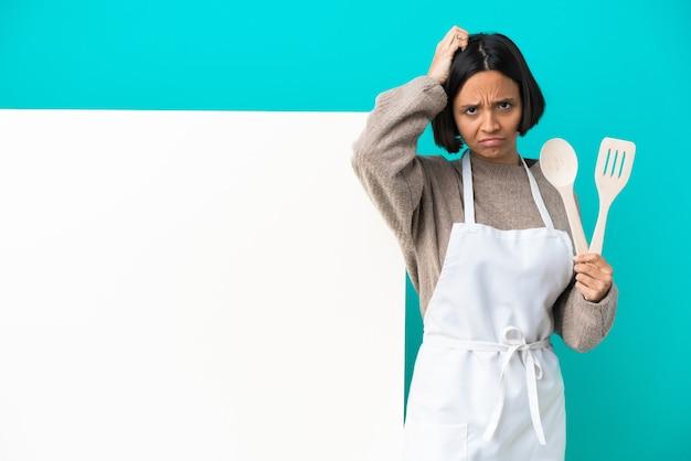 좌절감과 이해하지 못하는 표정으로 파란색 배경에 고립된 큰 현수막을 가진 젊은 혼혈 요리사 여성