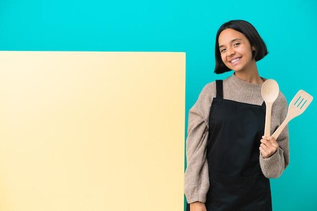Молодая женщина-повар смешанной расы с большим плакатом на синем фоне со скрещенными руками и нетерпением ждет