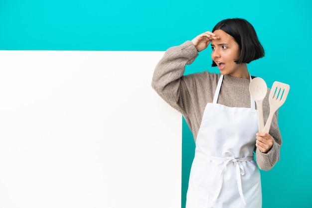 側を見ながら驚きの表情で青い背景に分離された大きなプラカードを持つ若い混血料理人女性