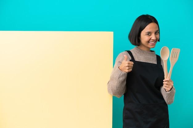 何か良いことが起こったので、親指を立てて青い背景に分離された大きなプラカードを持つ若い混血料理人の女性