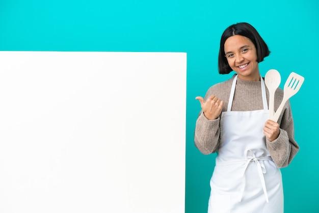 親指を立てるジェスチャーと笑顔で青い背景に分離された大きなプラカードを持つ若い混血料理人の女性