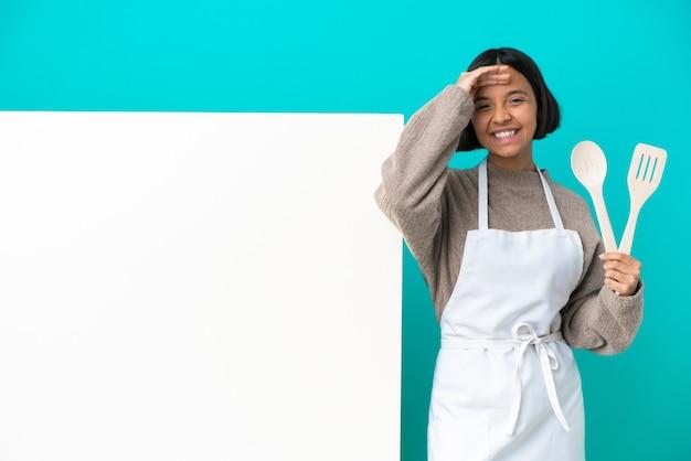 행복 한 표정으로 손으로 경례 고립 된 큰 현수막을 가진 젊은 혼합 된 경주 요리사 여자