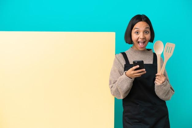 Молодая женщина-повар смешанной расы с большим изолированным плакатом удивлена и отправляет сообщение