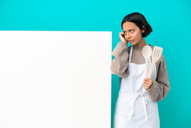 Young mixed race cook woman with a big placard isolated on blue background having doubts and thinking